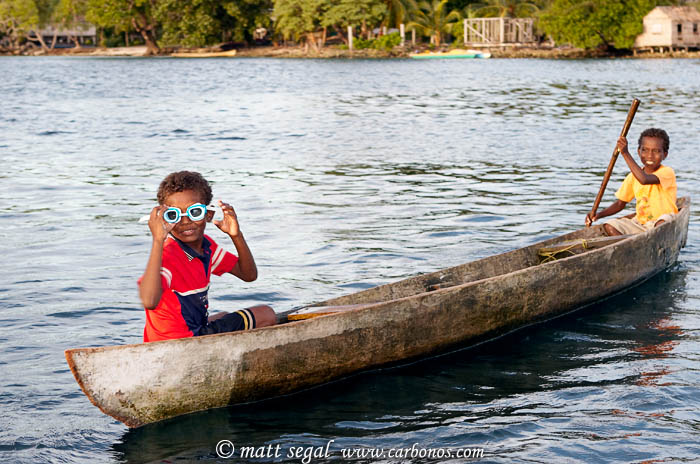 Image 992, Native village children of the Solomon Islands in a dugout canoe playing with swim goggles. Chief Luten's Village, Marovo Lagoon, New Georgia, Solomon Islands, Matt Segal, all rights reserved worldwide.  Keywords: Native, village, children, Solomon Islands, dugout, canoe, swim, goggles